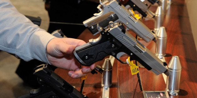 LAS VEGAS, NV - JANUARY 17:  Attendees try out Sig Sauer 1911 model pistols at the Sig Sauer booth at the National Shooting S