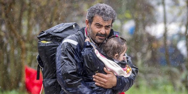 A migrant carries his child after crossing the Greek-Macedonian border, near Gevgelija, on November 27, 2015.Since last week,
