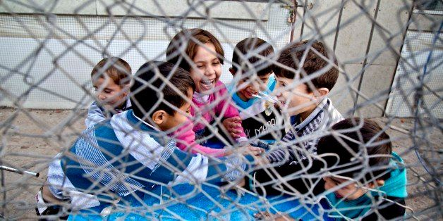 In this Saturday, Nov. 28, 2015 photo, Syrian refugee children play at a temporary refugee camp in Irbil, northern Iraq. Some