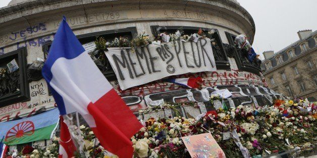 A picture taken on November 27, 2015, shows French national flags, candles and flowers at a makeshift memorial in Place de la