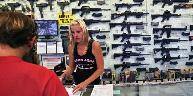In this July 20, 2014 photo, with guns displayed for sale behind her, a gun store employee helps a customer at Dragonman's, e