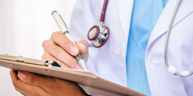 front view of doctor writing information on her folder with a pen