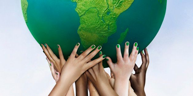 Multiracial hands holding green globe against sky background
