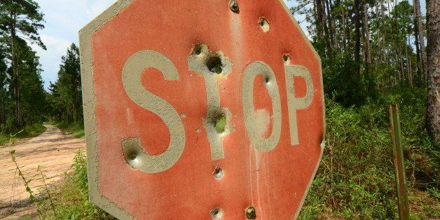 Angled photo of an old 'STOP' sign in a forest, with faded paint and various sized bullet holes. A dirt road at the left of t