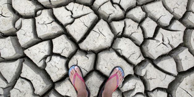 Large cracks in rock hard earth of water hole during dry season drought.