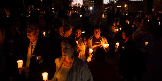 SAN BERNARDINO, CA - DECEMBER 7: People listen during a candlelight vigil held at the San Bernardino County Board of Supervis