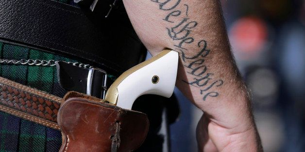 FILE - In this Jan. 26, 2015, file photo, Scott Smith, a supporter of open carry gun laws, wears a pistol as he prepares for