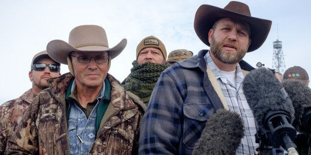 Ammon Bundy(R), leader of a group of armed anti-government protesters speaks to the media as other members look on at the Mal