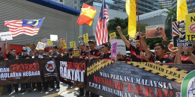 Dozens of Malaysian protesters shout slogans during a demonstration against the Trans-Pacific Partnership Agreement (TPPA), w