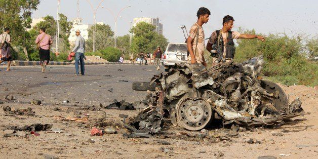 Fighters loyal to Yemen's President Abedrabbo Mansour Hadi look at the remains of a vehicle following a car bomb attack that