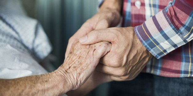 Close up of son holding his mothers hands in hospital