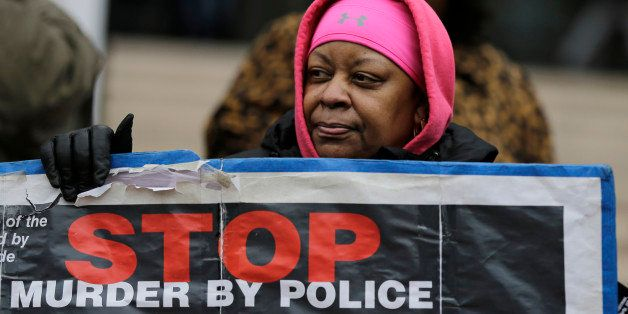 Loria Edwards protests outside the Cuyahoga County Justice Center, Tuesday, Dec. 29, 2015, in Cleveland. People marched peace