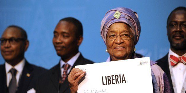 Liberian President Ellen Johnson-Sirleaf holds up an identification plaque signed by the World Trade Organisation (WTO) direc