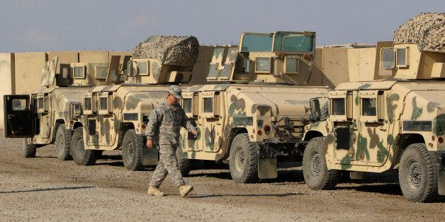 In this Nov. 7, 2011 photo, a U.S. army soldiers walks past military armored vehicles are ready to be shipped out of Iraq at