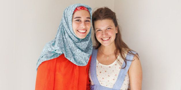 friendship of the religions concept: muslim and christian girl  standing together and smiling at camera
