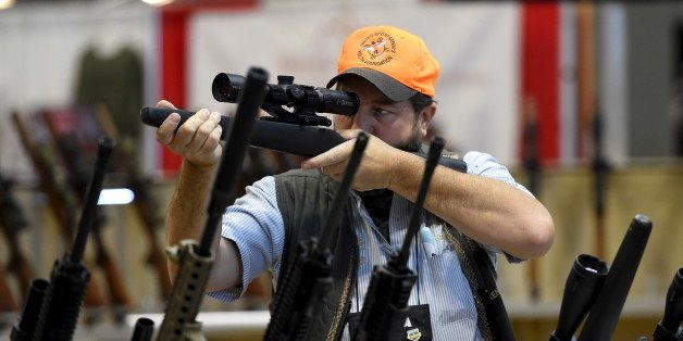 Brendan Walsh looks at a rifle scope in the trade booths showroom during the National Rifle Association's annual meeting in N
