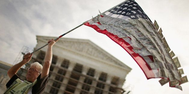 WASHINGTON, DC - OCTOBER 08:  David Barrows, of Washington, DC, waves a flag with corporate logos and fake money during a ral