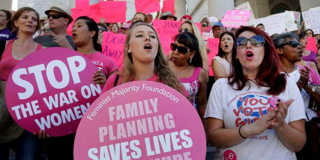 FILE - In this Sept. 9, 2015, file photo, Planned Parenthood supporters rally for women's access to reproductive health care