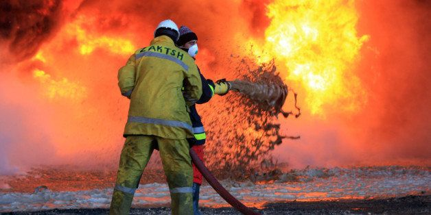 Libyan oil workers try to extinguish flames at an oil facility in northern Libya's Ras Lanouf region after it was set ablaze