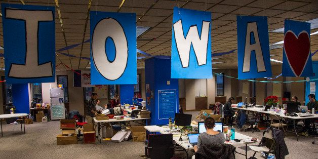 Banners spelling out Iowa hang from the ceiling as volunteers work at the Hillary for Iowa Campaign Headquarters in Des Moine