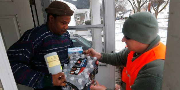 Louis Singleton receives water filters, bottled water and a test kit from Michigan National Guard Specialist Joe Weaver as cl