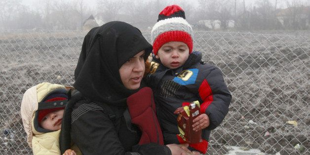 A Syrian refugee woman with babies walks towards the border with Serbia from the transit center for refugees near northern Ma