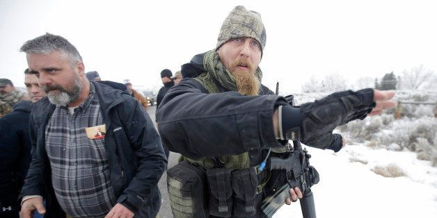"""A man standing guard pushes the media aside after members of the """"3% of Idaho"""" group along with several other organizations a"""