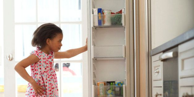 Girl (4-6) looking in kitchen fridge