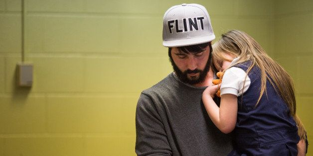 FLINT, MI - JANUARY 26:  Matt Hopper holds and comforts Nyla Hopper, age 5 of Flint, after she has her blood drawn to be test