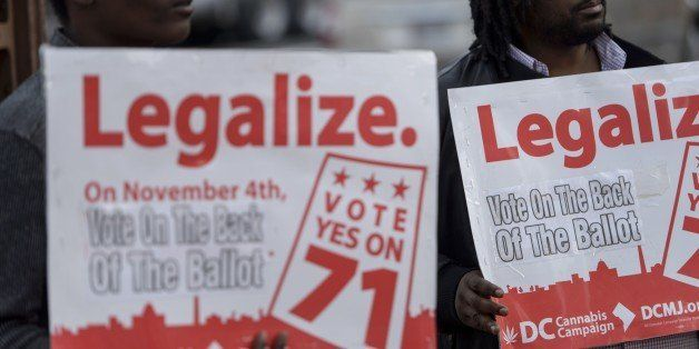 People hold signs for Ballot Initiative #71, the legalization of marijuana, on November 4, 2014 in Washington, DC. Voters aro