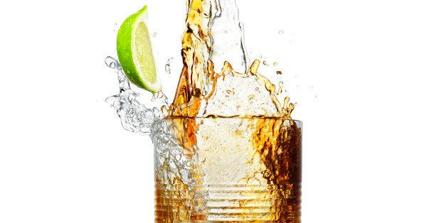 Making a big party splash of a mixture of a stream of clean clear alcohol and a stream of brown cola splashing and mixing a r
