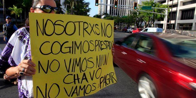 """A protestor holds a sign that reads in Spanish: """"We didn't take out a loan. We didn't see a dime. We're not going to pay."""" du"""