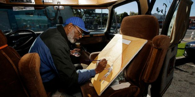 In this Nov. 10, 2015, photo, Ira Watkins, a homeless artist, works on a painting inside of the van where he works and lives