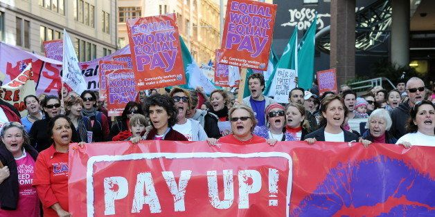 Protesters display banners and palcards as they take part in an 'Equal Pay' rally through Sydney on June 10, 2010. Unions hel