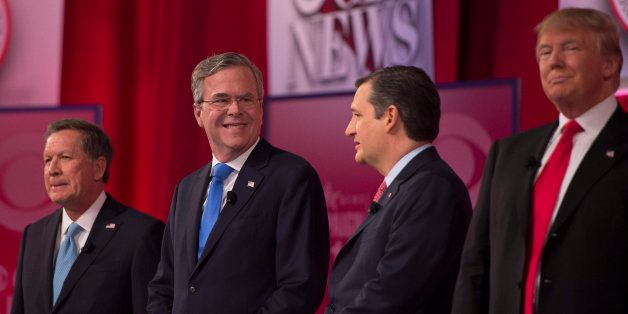 Republican presidential candidates John Kasich (L) and Donald Trump (R) look on as Jeb Bush (2nd-L) confers with Ted Cruz (2n