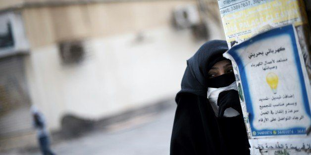 A Bahraini protester takes cover during clashes with riot police following a protest against the arrest of  Sheikh Ali Salman