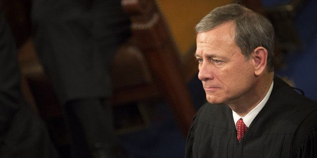 Chief Supreme Court Justice John Roberts listens as U.S. President Barack Obama delivers the State of the Union address to a