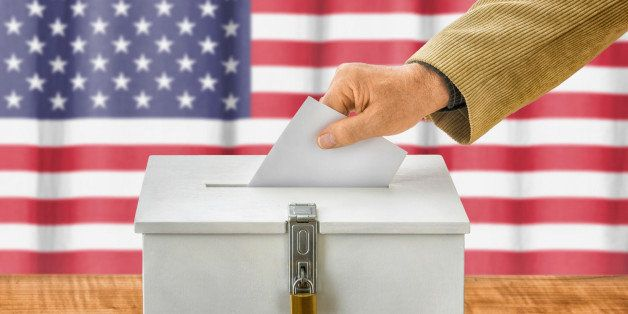Man putting a ballot into a voting box - USA