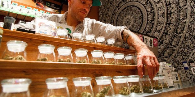 Shane Cavanaugh, owner of Amazon Organics, a pot dispensary in Eugene, Ore., arranges the cannabis display  in his store on M
