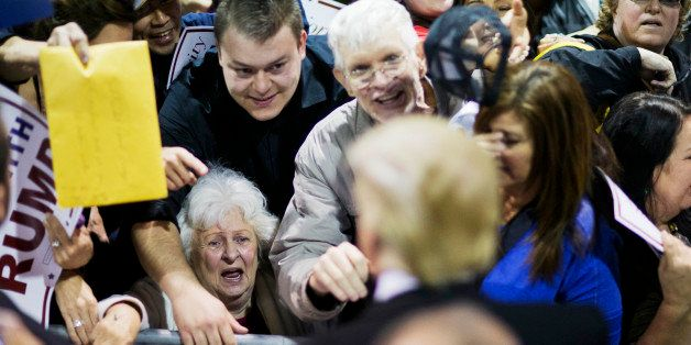 An audience member talks to Republican presidential candidate Donald Trump, left, as he signs autographs at a campaign event Sunday, Feb. 21, 2016, in Atlanta. (AP Photo/David Goldman)