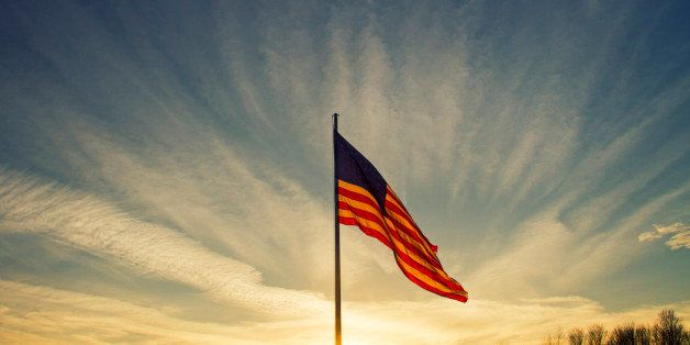 The sun sets behind a large flapping American flag under a blue sky.