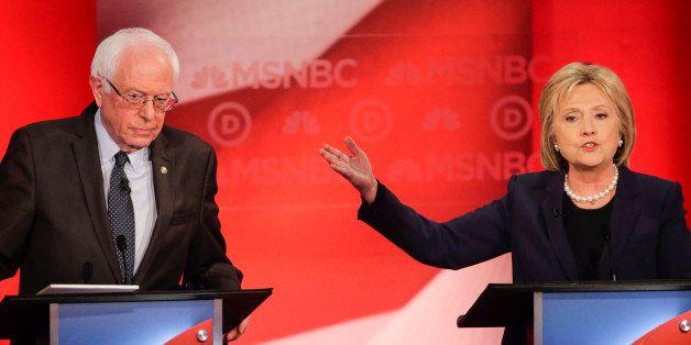 Democratic presidential candidate, Sen. Bernie Sanders, I-Vt,  listens as Democratic presidential candidate, Hillary Clinton