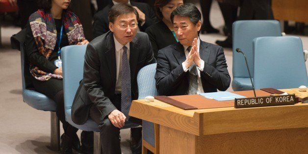 South Korea's delegation to the UN lead by Ambassador Oh Joon (R) talkS before a vote during a United Nations Security Counci