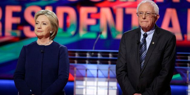 Democratic presidential candidates Hillary Clinton, left, and Sen. Bernie Sanders, I-Vt., stand on stage before a Democratic