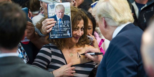 Republican presidential candidate Donald Trump autographs a supporter's chest following his speech at a campaign rally at Pri