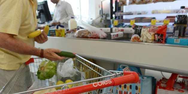 A customer unloads items from his shopping cart at a checkout counter in a Coles supermarket, operated by Wesfarmers Ltd., in