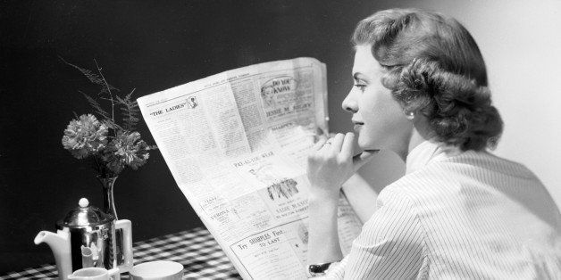 A woman wearing a striped shirt blouse reads a newspaper over the breakfast table before tackling her boiled egg and coffee.
