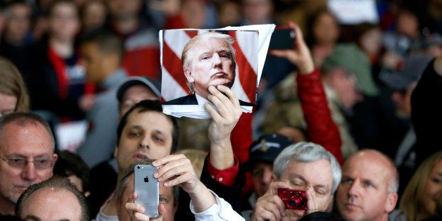 A supporter of Republican presidential candidate Donald Trump holds up a photo of Trump during a rally Sunday, March 13, 2016