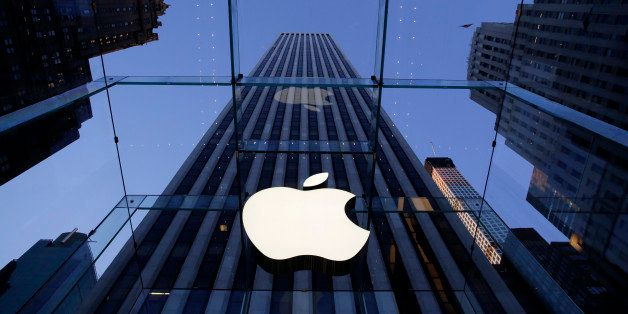 In this Sept. 5, 2014 photo, the Apple logo hangs in the glass box entrance to the company's Fifth Avenue store, in New York.