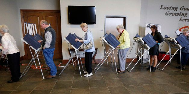 Voters fill the electronic voting machines to cast their ballots during the primary election at the precinct in the Highland